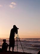 Photographer taking pictures on Banzai Pipeline, a surf reef break in Pupukea, O'Ahu, Hawai'i