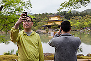 Asian tourists take photos and selfies with smart phones at Kinkaku-ji or the Golden Temple in Kyoto, Japan Sunday April 24th 2016. Due to growing regional prosperity and a weak Yen tourism to Japan is increasing. Over 24 million people are expected to visit the country in 2016