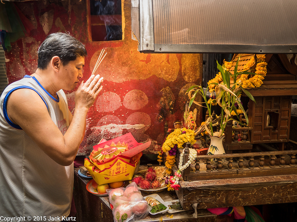 28 AUGUST 2015 - BANGKOK, THAILAND:     A man prays at a small shrine in Bangkok's Chinatown on Hungry Ghost Day. Mahayana  Buddhists believe that the gates of hell are opened on the full moon of the seventh lunar month of the Chinese calendar, and the spirits of hungry ghosts allowed to roam the earth. These ghosts need food and merit to find their way back to their own. People help by offering food, paper money, candles and flowers, making merit of their own in the process. Hungry Ghost Day is observed in communities with a large ethnic Chinese population, like Bangkok's Chinatown.    PHOTO BY JACK KURTZ