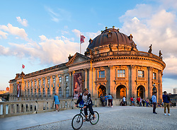 Late summer afternoon sun shining on Bode Museum with  public relaxing on Museum Island in Berlin, Germany