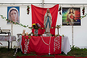 A statuette of the Virgin Mary surrounded by other Catholic iconography such as rosary beads and prayer cards inside a tent at Appleby Horse Fair, the biggest gathering of Gypsies and travellers in Europe, on 14th August, 2021 in Appleby, United Kingdom. Appleby Horse Fair attracts thousands from Gypsy, Romany, and traveller communities annually, making it the biggest gathering of its kind in Europe. Generally held for a week every June, the fair was postponed in 2020 and pushed forward to August in 2021 due to Coronavirus.