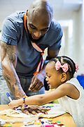 A young father does some art work with his young daughter during a family visit in HMP Brixton, South London on the 26th of July 2016, London United Kingdom. The Prisoner Advice & Care Trust (PACT) organise special family days that help the men inside the prison connect with and support their partners and children on the outside. (photo by Andy Aitchison)