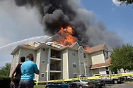 Residents watch as firefighters work to put out a fully-engulfed fire at the Tivoli apartments across from the University of Central Florida campus in Oviedo, Fla., Sunday, July 12, 2015. ( Photo/Phelan M. Ebenhack)