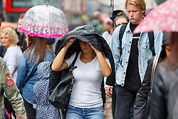 © Licensed to London News Pictures. 19/08/2016. London, UK. People take shelter from the rain on Oxford Street in London on 19 August 2016. Photo credit: Tolga Akmen/LNP