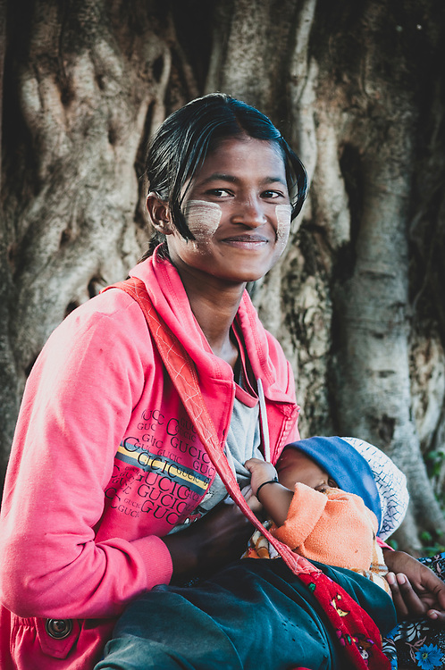 Kalaw, Myanmar - October 31, 2011: A young woman nurses her child in the town of Kalaw, in Shan State.