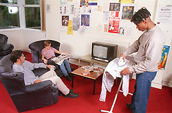 Multiracial group of teenagers in communal lounge in hostel ironing clothes; watching television and reading newspaper,