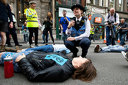 © Licensed to London News Pictures. 15/07/2019. London, UK.A police officer talks to an Extinction Rebellion protester outside The Royal Courts of Justice. They are campaigning against climate change.  Photo credit: George Cracknell Wright/LNP