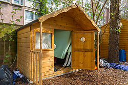 A small wooden wendy house in a section of an allotment reserved as a children's play area appears to have become the residence or storage shed of a homeless individual, with what appear to be mattresses and bedding stuffed inside.. Munster Square, Camden, March 18 2019.