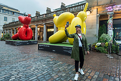 © Licensed to London News Pictures. 07/10/2021. LONDON, UK. A woman takes a selfie with (L to R) Stretching Balloon Dog and Downward Balloon Dog by the artist known as Whatshisname (real name Sebastian Burdon) installed in Covent Garden. In total, four colourful balloon dogs are on display until the end of October.  The public are encouraged to take photos and post them to social media with a hashtag #castleforbluecross and Castle Fine Art will donate £1 to the Blue Cross animal welfare charity for each post..  Photo credit: Stephen Chung/LNP