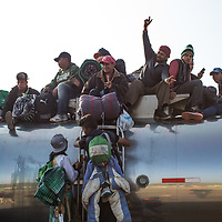 Central American migrants from the migrant caravan climb on top of a tanker vehicle to ride the road between Querétaro and Irapauto, Guanajuato.