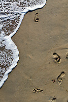 17 May 2003: Life in Orange County. Footprints in the sand along the shoreline next to the Pacific Ocean waters off the coast of California. Stock Photo,art,graphic,book,sand,surf,spiritual,water.  .
