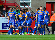 Jean-Louis Akpa Akpro celebrates scoring the first goal with team mates during the Sky Bet League 2 match between Cheltenham Town and Shrewsbury Town at Whaddon Road, Cheltenham, England on 25 April 2015. Photo by Alan Franklin.