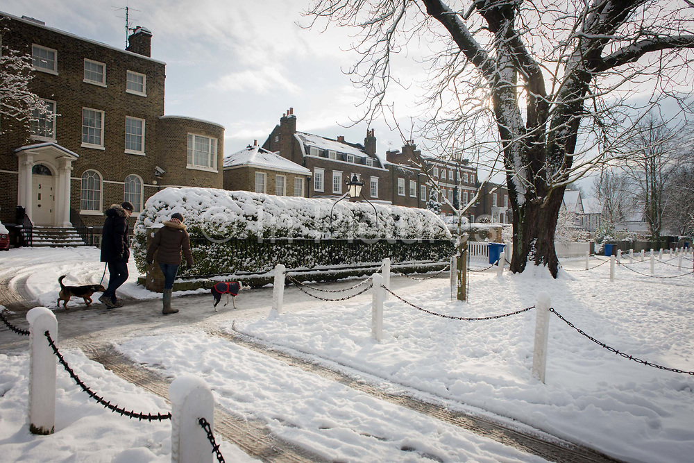 "Dog walkers pass-by a Dulwich Village landscape during mid-winter snow. With sunshine now thawing the pavements after a week of freezing temperatures, the paths are now turning to slush, an excellent day for a winter walk with dogs and children. Dulwich Village is an area of Dulwich in South London's SE21 postcode area in England It is located in the London Borough of Southwark. ""Dulwich Village"" is also the name of one of the High Streets in the area. Residents in Dulwich Village have to pay ground rent to the Dulwich Estate a landowning charitable organisation. The first documented evidence of Dulwich is as a hamlet outside London in 967AD, granted by King Edgar to one of his thanes Earl Aelfheah."
