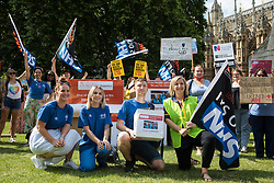 London, UK. 20th July, 2021. NHS workers from the grassroots NHSPay15 campaign pose outside Parliament before a march to 10 Downing Street to present Matthew Tovey's petition signed by over 800,000 people calling for a 15% pay rise for NHS workers. At the time of presentation of the petition, the government was believed to be preparing to offer NHS workers a 3% pay rise in 'recognition of the unique impact of the pandemic on the NHS'.