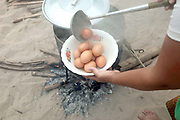 Cooking hardboiled eggs for a snack to sell at the small monthly market at the Khmu village of Ban Phatao, Phongsaly province, Lao PDR. The market traders travel along the Nam Ou visiting different villages selling every kind of Chinese and Vietnamese product that one might need - like biscuits and flip flops, washing powder and salt. Ban Phatao will soon be temporarily relocating away from the Nam Ou river due to the construction of the Nam Ou Cascade Hydropower Project Dam 5.