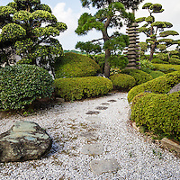 """Yugyoji Zen Garden - Shojiko-ji Temple, commonly known as """"Yugyoji"""" temple in Fujisawa has been selected as one of the """"100 Most Scenic Places in Japan"""".  Yugyoji holds has an important historic and religious significance as the headquarters of the Ji Sect, an offshoot of Pure Land Buddhism.  The temple was founded during the Kamakura Period in the 1200s.  The main hall of the temple has an ornate interior and to its left is the Chujakumon Gate, with roof tiles indicating approval by the Imperial family.  Beyond it is a beautiful and tranquil garden, filled with statues, a koi pond and landscaping in the traditional Japanese style accentuated by meticulously crafted and maintained trees and plants."""