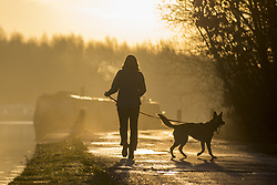December 17, 2018 - Leeds, Yorkshire, UK - A woman walks her dog at Lemonroyd lock on the Aire & Calder Navigation canal in Woodlesford, Leeds, at sunrise this morning. (Credit Image: © Andrew Mccaren/London News Pictures via ZUMA Wire)