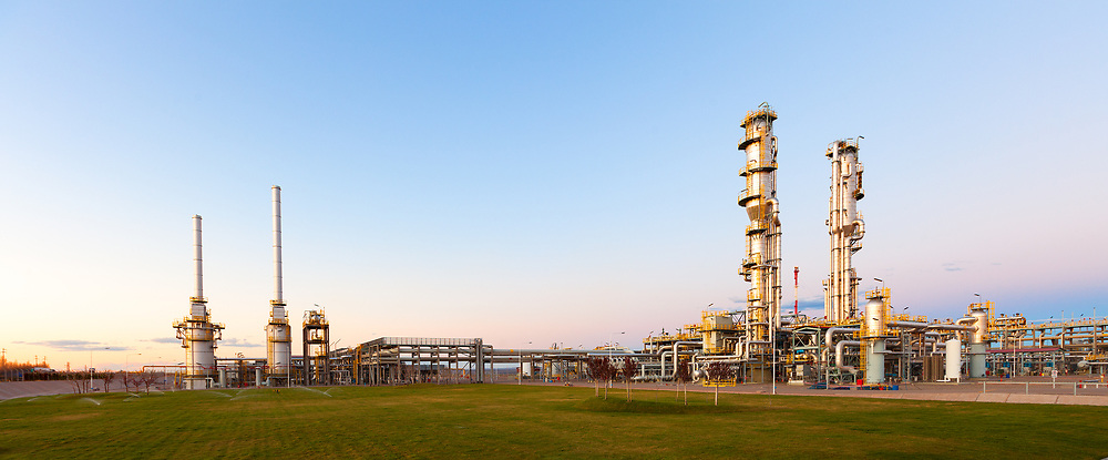 View of a gas refinery plant illuminated at dusk.