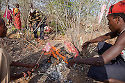 A man makes a fire after slaughtering a pregnant cow that got critically bloated after swallowing plastic bags in a village near Narouk, Kenya. In the dry, near desert conditions of drought stricken Kenya, discarded plastic bags are eaten by cows while grazing. Maasai wealth is derived from the cattle owned, the land, and the number of children born to support the family busines, which is cattle and goats.