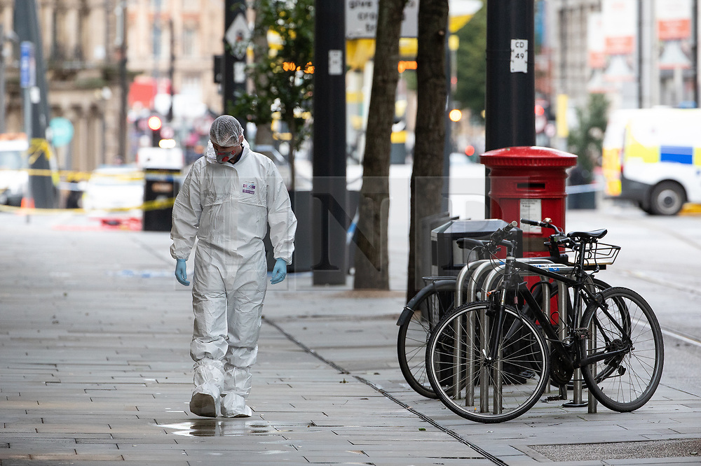 © Licensed to London News Pictures. 11/10/2019. Manchester, UK. A forensic scenes of crime examiner searches the pavement adjacent to a pillar box , made famous for being photographed still standing amongst rubble after a terror attack by the IRA in the same part of the city in 1996 . Terrorism Police are investigating after four people were stabbed during a single attack at the Arndale Centre in Manchester City Centre . Photo credit: Joel Goodman/LNP