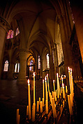 Thin, tall candles burn inside the main room of an old church or cathedral in France