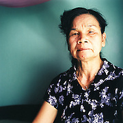 """""""I was born in 1949 in the countryside outside Hue, where I lived with my parents.  I joined the war when I was about 15 years old.  At that age, I could understand, could see that the Americans had come and were trying to control and take my country.  At that moment every woman and man joined the war, and I wanted to as well.<br /> <br /> """"When I joined the war, I joined the group that gathered information. We would go around and see what the Americans were doing, and then we would send that information to the leader.  A bit later, I joined the group that rounded up other women to join the war.<br /> <br /> """"At the time, all the women and I were very young, and we didn't know really about the war and its plan.  We just had to believe in the government, that everything would be okay.   If we had any problems, even though we didn't really know the grand plan or the next step, we were always happy to be fighting for our country.  We were ready to die.<br /> <br /> """"The past time in the war, there were many difficulties.  Everyone was very poor, but everyone loved each other and tried to trust each other.  Now, we have freedom, maybe life is easier, but money controls many things.  So when I talk to my daughters about the war, I tell them how to love and trust other people.  Tell them how people followed the laws, the rules of the government.""""<br /> <br /> Hoàng Thi No, born in 1949, photographed in her bedroom in Hue, Vietnam with her helmet from the American war. July 2010."""
