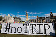 """No TTIP European Day of Action – as part of a day of protest across the EU.  The Transatlantic Trade and Investment Partnership (TTIP) is supposed to be 'free trade' deal and is currently being negotiated by the EU and US. Protestors are concerned that the """"deal will give big business more power over society, the environment, public services and democracy"""". Parliament Square, London 11 Oct 2014."""