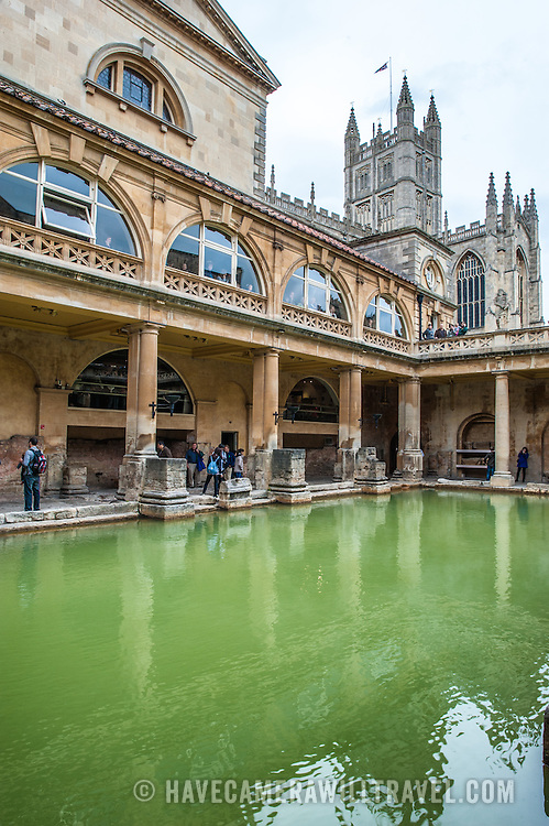 A view of the waters of the historic Roman Baths in Bath, Somerset, with Bath Cathedral visible in the background.