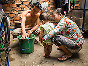 24 FEBRUARY 2015 - PHNOM PENH, CAMBODIA:  A man grates papaya for Khmer salads while his child and wife talk to him in the White Building. The White Building, the first modern apartment building in Phnom Penh, originally had 468 apartments, and was opened the early 1960s. The project was overseen by Vann Molyvann, the first Cambodian architect educated in France. The building was abandoned during the Khmer Rouge occupation. After the Khmer Rouge were expelled from Phnom Penh in 1979, artists and dancers moved into the White Building. Now about 2,500 people, mostly urban and working poor, live in the building. Ownership of the building is in dispute. No single entity owns the building, some units are owned by their occupants, others units are owned by companies who lease out apartments. Many of the original apartments have been subdivided since the building opened and serve as homes to two or three families. The building has not been renovated since the early 1970s and is in disrepair. Phnom Penh officials have tried to evict the tenants and demolish the building but residents refuse to move out.  PHOTO BY JACK KURTZ
