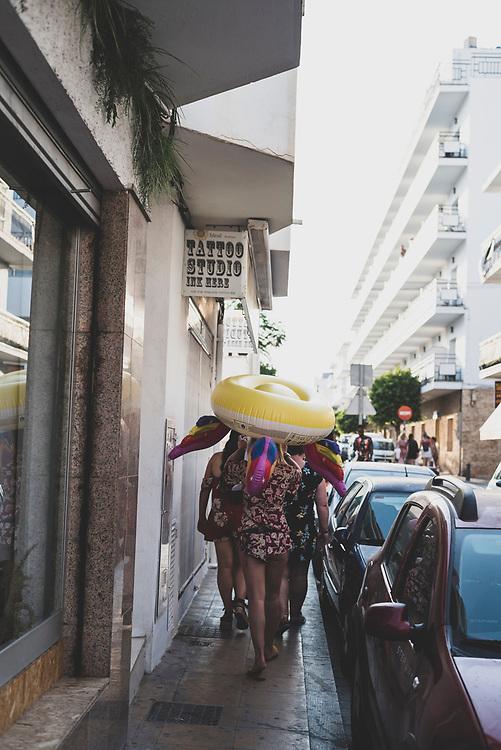 Sant Antoni de Portmany, Ibiza, Spain - August 3, 2018: Young women walk through town after some time at the beach in Sant Antoni (San Antonio), Ibiza.