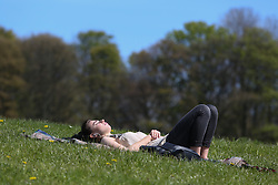 © Licensed to London News Pictures. 04/05/2016. Leeds, UK. A woman bathes in the bright warm sunshine in Hyde Park in Leeds, West Yorkshire. Britain is experience warmer weather this week with temperatures to rise to 23 degrees celsius this weekend. Photo credit : Ian Hinchliffe/LNP