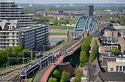 Nederland, Nijmegen: 1-5-2018 Uitzicht op het centum van Nijmegen richting Betuwe . Spoorbrug met fietsbrug de snelbinder, nieuwbouw Handelskade,  rivier de waal en de nevengeul, spiegelwaal zijn te zien . FOTO: FLIP FRANSSEN