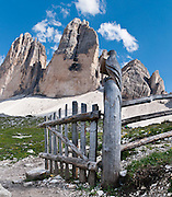 """A carved bird decorates a gate. Hike for spectacular views around Tre Cime di Lavaredo (Italian for """"Three Peaks of Lavaredo,"""" also called Drei Zinnen or """"Three Merlons"""" in German), which are distinctive icons of the Alps, in the Sexten Dolomites of northeastern Italy, Europe. Until 1919 the peaks formed part of the border between Italy and Austria. Now they lie on the border between the Italian provinces of South Tyrol and Belluno and still are a part of the linguistic boundary between German-speaking and Italian-speaking majorities. Cima Grande rises to 2999 meters (9839 feet), between Cima Piccola  2857 m (9373 ft) and Cima Ovest  or """"Western Peak"""" 2973 m (9754 ft). The Dolomites were declared a natural World Heritage Site (2009) by UNESCO. Panorama stitched from 2 overlapping photos."""
