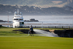 June 11, 2019 - Pebble Beach, CA, U.S. - PEBBLE BEACH, CA - JUNE 11:  A course worker waters the 18th fairway during the practice round for the 2019 US Open on June 11, 2019, at Pebble Beach Golf Links in Pebble Beach, CA. (Photo by Brian Spurlock/Icon Sportswire) (Credit Image: © Brian Spurlock/Icon SMI via ZUMA Press)