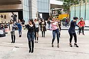 Filipino domestic workers gather on their day-off and hold an impromptu line dance in Central District, Hong Kong. Approximately 130,000 Filipino domestic servants work in Hong Kong and all have Sundays off.