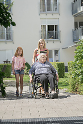 Senior woman on wheelchair with daughter and granddaughter at rest home park, Bavaria, Germany