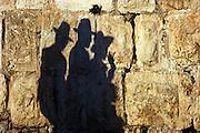 Israel, Jerusalem silhouette of orthodox jews on the walls of Jerusalem stone
