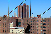 cables from the Brooklyn Bridge looking towards mid town New York city with Empire state building and other high rise buildings