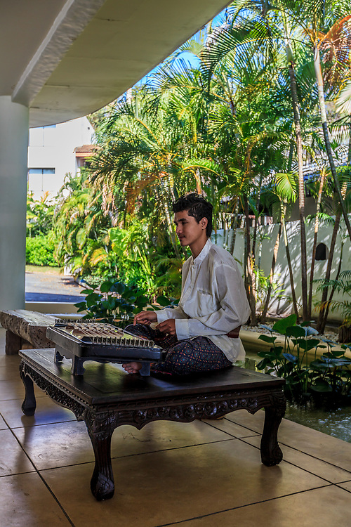 A khim musician in Phuket, Thailand. Hammered dulcimers, like the khim, represent the ancient invention of strings. The western piano was developed from a hammered dulcimer.  Players of these dulcimers are highly valued for their high playing skills.