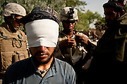 Marines detain two men suspected of emplacing an improvised explosive device near Combat Outpost Coutu, in Marjah, Helmand Province.
