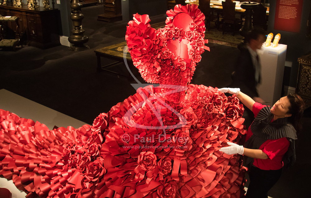 """Sotheby's, London, January 14th 2016. Paper artist ZOE BRADLEY exhibits spectacular paper sculptures inspired by the fashion in old master paintings. Her astonishing works are exhibited alongside 460 royal and aristocratic heirlooms  that will appear in Sotheby's """"Of Royal and Noble Descent"""" auction to be held between 14th and 18th January. PICTURED: Paper sculptor Zoe Bradley puts the finishing touches to her installation , a monumental red ruffle gown, made up of 5,940 ruffles of paper. ///FOR LICENCING CONTACT: paul@pauldaveycreative.co.uk TEL:+44 (0) 7966 016 296 or +44 (0) 20 8969 6875. ©2015 Paul R Davey. All rights reserved."""