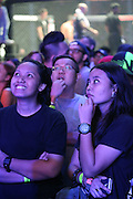 """Two young women watch the video screens ecstatic as heroes battle it out in the ring<br /><br />MMA. Mixed Martial Arts """"Tigers of Asia"""" cage fighting competition. Top professional male and female fighters from across Asia, Russia, Australia, Malaysia, Japan and the Philippines come together to fight. This tournament takes place in front of a ten thousand strong crowd of supporters in Pelaing Stadium. Kuala Lumpur, Malaysia. October 2015"""