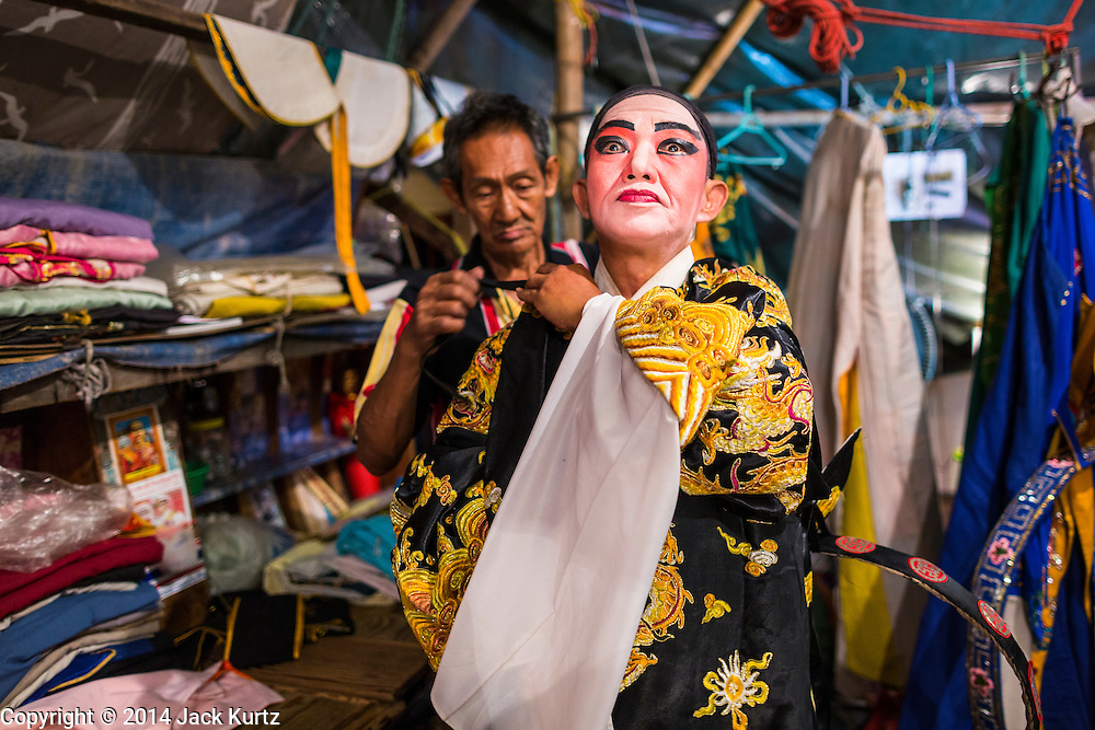 """19 AUGUST 2014 - BANGKOK, THAILAND:  Members of the Lehigh Leng Kaitoung Opera troupe put on their costumes before a performance at the Chaomae Thapthim Shrine, a small Chinese shrine in a working class neighborhood of Bangkok. The performance was for Ghost Month. Chinese opera was once very popular in Thailand, where it is called """"Ngiew."""" It is usually performed in the Teochew language. Millions of Chinese emigrated to Thailand (then Siam) in the 18th and 19th centuries and brought their culture with them. Recently the popularity of ngiew has faded as people turn to performances of opera on DVD or movies. There are still as many 30 Chinese opera troupes left in Bangkok and its environs. They are especially busy during Chinese New Year and Chinese holiday when they travel from Chinese temple to Chinese temple performing on stages they put up in streets near the temple, sometimes sleeping on hammocks they sling under their stage. Most of the Chinese operas from Bangkok travel to Malaysia for Ghost Month, leaving just a few to perform in Bangkok.        PHOTO BY JACK KURTZ"""