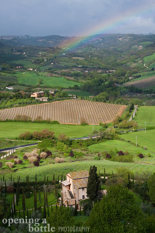 A spring rain cloud brings a rainbow to the green countryside surrounding Orvieto, Umbria, Italy.