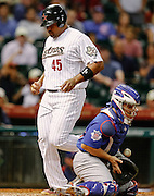 May 23, 2012; Houston, TX, USA; Houston Astros first baseman Carlos Lee (45) scores as Chicago Cubs catcher Koyie Hill (55) blocks the throw home during the eighth inning at Minute Maid Park. Mandatory Credit: Thomas Campbell-US PRESSWIRE
