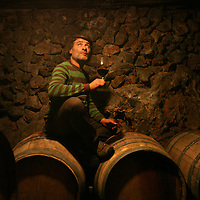 SETTLER'S BOUTIQUE WINE 2009...Yoram Cohen, Winery manager of Tanya boutique winery, sits on wine barrels and drinks a glass of wine in the West Bank Jewish settlement of Ofra, October 2009.
