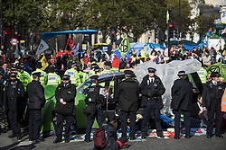 © Licensed to London News Pictures. 10/10/2019. London, UK. Police move in to move Extinction Rebellion activists who refuse to move from the roads around Trafalgar Square in Westminster, central London where they have been demonstrating for a fourth day running. The climate change group have blockaded the Westminster area, demanding that the government takes immediate and decisive action on climate change. Photo credit: Ben Cawthra/LNP