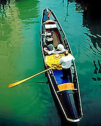 A gondolier guides his gondola through a canal in Venice, Italy