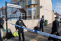 © Licensed to London News Pictures. 22/03/2021. London, UK. Police officers stand inside a cordon following a disturbance at a premises in Granville Avenue, Hounslow. Metropolitan Police attended at approximately 03:20GMT and found two men suffering stab injuries. A man, aged in his 20s, was treated at the scene but died at 04:23GMT. The second man, also aged in his 20s, was taken to hospital. His injuries were assessed and he has since been discharged. Photo credit: Peter Manning/LNP