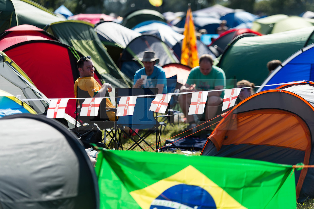 © Licensed to London News Pictures. 13/06/2014. Isle of Wight, UK.   English flags contrast with the Brazillian flag at as festival goers relax in the early morning sun in their campsite at the Isle of Wight Festival 2014.    Today is expected to be the hottest day of the year in the UK and England is set to play Italy in the World Cup .   The Isle of Wight festival is an annual music festival that takes place on the Isle of Wight. Photo credit : Richard Isaac/LNP